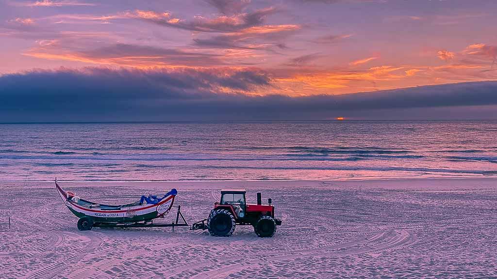 Abendstimmung in Costa de Lavos mit Meer im Hintergrund und Traktor mit angehängtem Fischerboot im Vordergrund